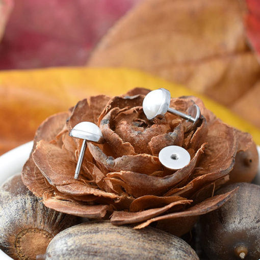Half Pearl ComfyEarrings on natural fall decor.