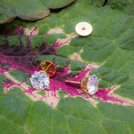 6.0 mm Crystal Gold Prong ComfyEarrings on a purple and green leaf.