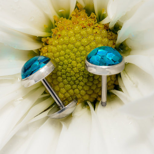 Blue Funfetti ComfyEarrings on white flower with water drops.