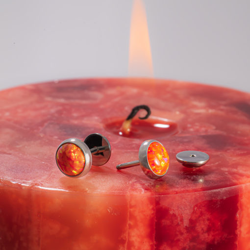 Fire Opal ComfyEarrings on lit red and orange candle